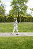 Woman outdoors texting on her mobile phone, walking in the park photo