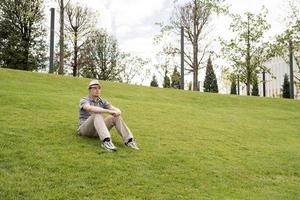 Young thoughtful man sitting on the grass in the park photo