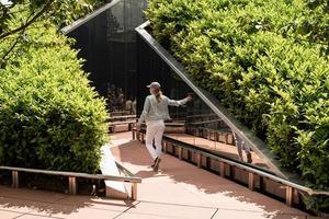 Mujer joven caminando en el laberinto de espejos, mirando el reflejo foto