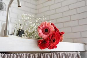 Close up of red and pink gerbera daisies in a kitchen sink photo