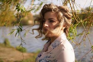 Retrato de mujer de perfil descansando sobre la naturaleza cerca del río foto
