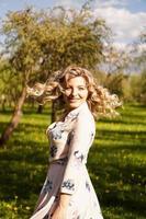 feliz, mujer joven, con, pelo rubio, llevando, un, vestido, posar, aire libre foto