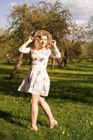 Sonriente mujer de verano con sombrero de paja en el parque foto