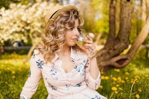 Beautiful young woman with blonde hair in straw hat drinks wine photo