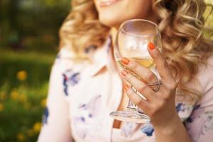 rubia feliz sosteniendo una copa de vino blanco foto
