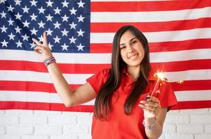 Beautiful woman holding a sparkler on US flag background photo