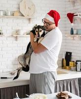 Handsome hipster with his dog cooking christmas cake in a kitchen. photo