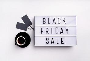 Black Friday Sale words on lightbox with cup of coffee and black photo