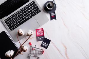 Black Friday Sale words on the tag, workspace with laptop, notebook photo