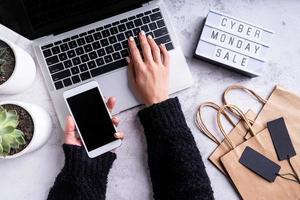 Top view of woman hands shopping online, Cyber Monday Sale text photo