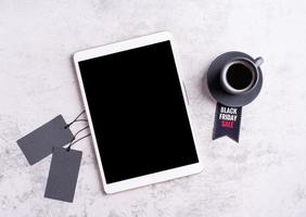 Black Friday Sale words on the tag, tablet and cup of black coffee photo