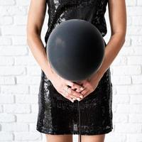 Woman in black dress holding black balloon in front of her face photo