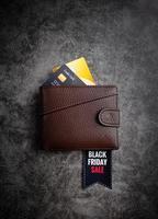Cartera de cuero marrón con texto Black Friday Sale en una etiqueta y crédito foto