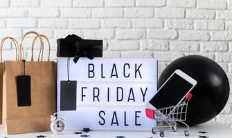 Black friday Sale words on lightbox with black price tag and gifts photo