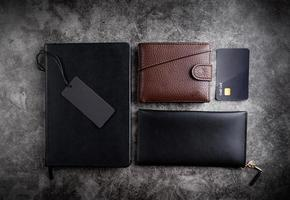 Black notebook, wallets, credit cards and blank price tag top view photo