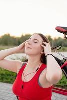 Teenage girl sitting next to her bike listening to the music photo