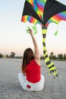 Young woman flying a kite in a public park at sunset photo