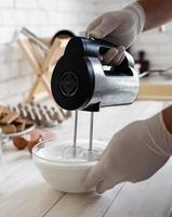 Batir las claras de huevo y el azúcar granulada sobre la mesa de madera blanca foto