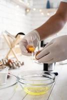 Manos del hombre separando la yema y la clara de la cáscara de huevo en la cocina foto