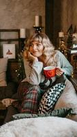 Young woman with cup of tea in Christmas cozy interior photo