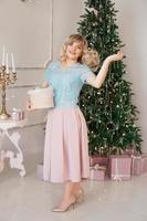 mujer joven decora el árbol de navidad con juguetes de navidad foto