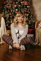 Cheerful smiling blonde woman decorates Christmas tree with ball photo