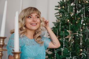 Young woman decorates Christmas tree with Christmas toys photo