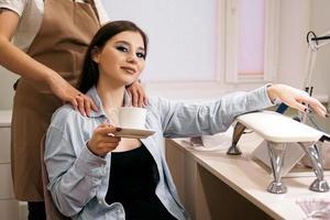 mujer recibiendo manicura y masaje al mismo tiempo en un salón foto