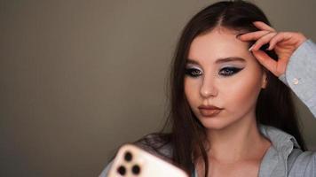 Modelo atractivo joven hacer un selfie después del maquillaje en el estudio de belleza foto