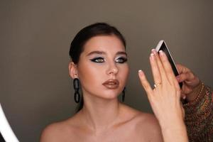 Make up artist taking mobile photo for the model with makeup