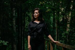 Young woman - close portrait in a dark forest. Woman in black shirt photo