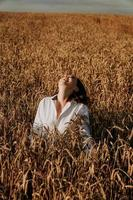Summer nature, happy young woman in the ears of a rye field photo