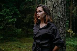 mujer joven - retrato cercano en un bosque oscuro. mujer en camisa negra foto