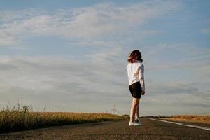 mujer con una camisa blanca camina por la carretera entre los campos foto