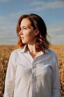 Red-haired girl in a white shirt. She in rye field on a sunny day photo