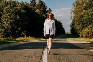 mujer con una camisa blanca camina por la carretera entre el bosque foto