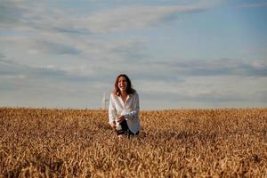 mujer corre en un campo de trigo en un día de verano. concepto de felicidad y alegría foto