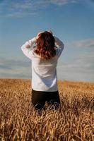 Woman in rye field. View from the back. The concept of harmony photo