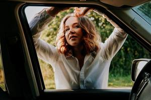 Woman in the car window. Trips out of town. Travel and joy concept photo