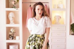 Happy young woman dressing up. Dressing room in pink photo