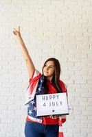 Woman with American flag holding lightbox with words Happy 4 July photo