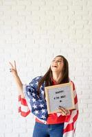 Woman with American flag holding letter board with words Happy 4th July photo