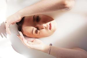 Girl in bath with milk. Spa treatments for skin rejuvenation. photo