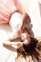 Young woman, beautiful sunlight. She lies on a wooden floor photo