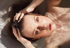 Top view of gorgeous young woman taking a bath photo