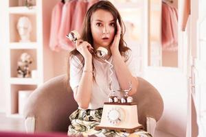 Girl talking on retro telephone in pink dressing room. Pin-up emotion photo