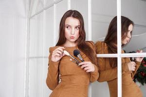 Artista de maquillaje sosteniendo una brocha para polvos, reflejo en el espejo foto