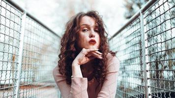 Retrato de moda de moda joven sentado cerca de la red rabitz foto