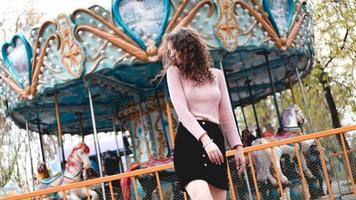 Girl chilling in amusement park in weekend morning. Laughing model photo