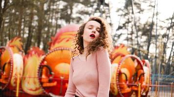Mujer joven inconformista posando al aire libre en el fondo de carruseles foto